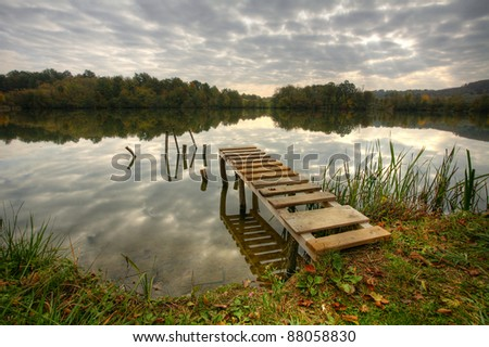 Beautiful lake with pier on cloudy day - stock photo