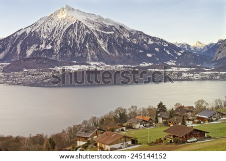 Beautiful lakeview over Swiss Alps mountains in a Swiss village near the Thun lake in winter - stock photo