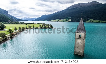 Beautiful landcape with the clock tower in Reschensee. Location Reschenpass on the border between the South Tyrol, Italy and Austria.