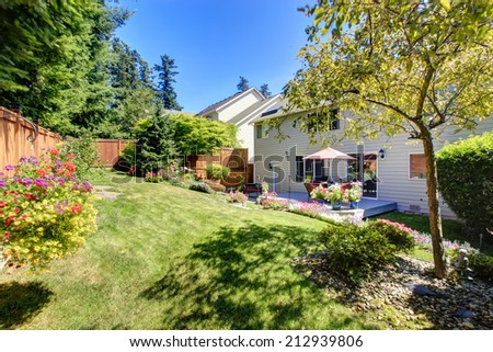 Beautiful landscape design for backyard garden and patio area on walkout deck - stock photo