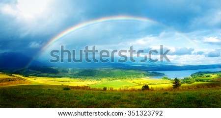 Beautiful landscape, green and yellow meadow and lake with mountain on background with a rainbow in the sky. - stock photo
