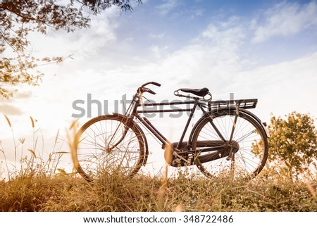 beautiful landscape image with vintage Bicycle at sunset