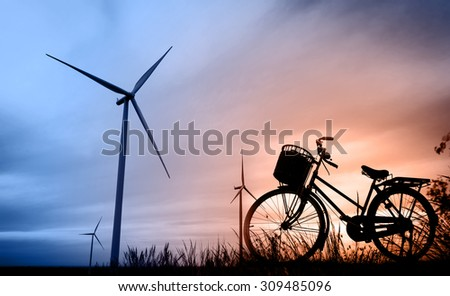 beautiful landscape image with Windturbine and bicycle at the sunrise - stock photo