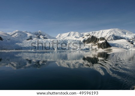 Beautiful landscape in Antarctica in morning light. Some snow covered mountains and reflections on water. - stock photo
