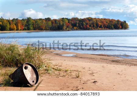 Beautiful landscape is ruined by discarded industrial barrel washed ashore.  Lake Superior in Upper Peninsula, Michigan is alive with Autumn color. - stock photo