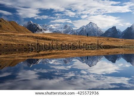 Beautiful landscape. Mountain Lake with mirrored reflection. Man stands on a hill. Koruldi Lake. Caucasus, Georgia, Zemo Svaneti - stock photo