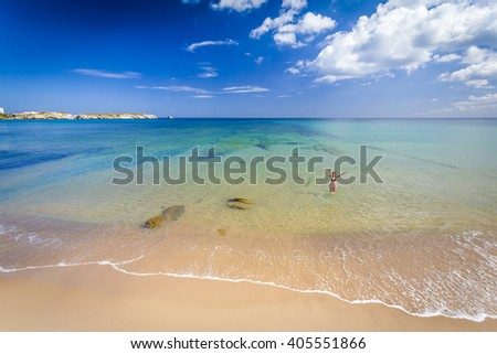 Beautiful landscape of a portuguese beach with a woman on the sea - stock photo