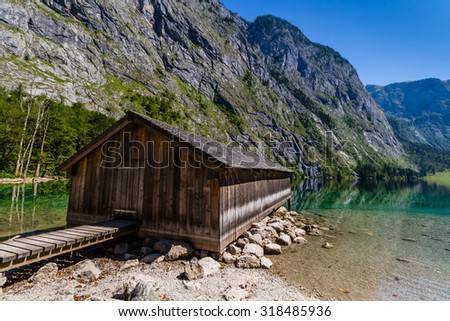 Beautiful landscape of alpine lake with crystal clear green water and mountains in background, Obersee, Germany