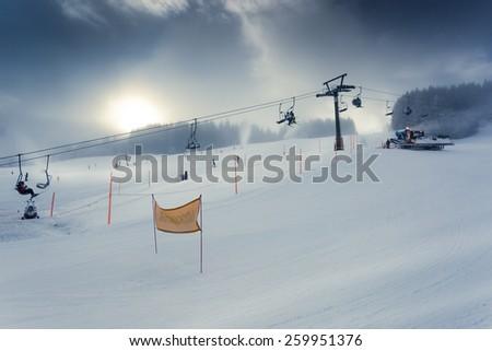Beautiful landscape of Alpine ski slope with working ski lift - stock photo