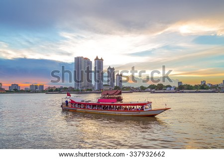 Beautiful landscape of business city with river ferry boat in the foreground at twilight.
