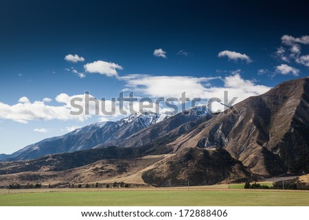 Beautiful landscape of grass field and mountain with blue sky at Arthur's Pass National Park, South Island, New Zealand