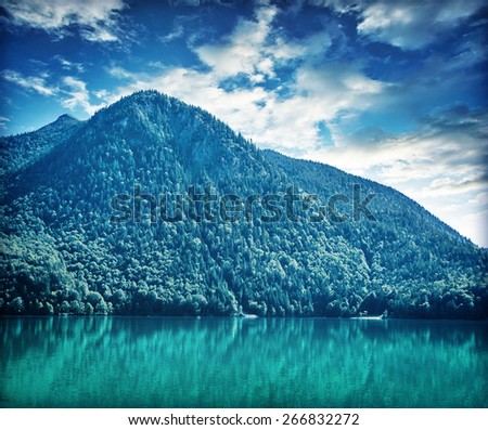 Beautiful landscape of great mountain covered with thick pine forest over lake, amazing panoramic scene of Alps, Austria, Europe - stock photo