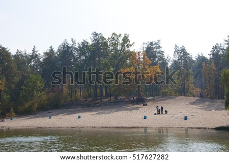 beautiful landscape of lake or river water green autumn forest or wood and sunny sky in park outdoor on natural background with people on sandy beach