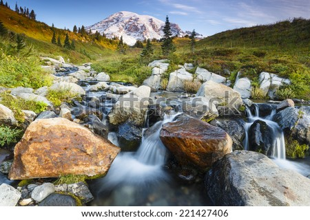 Beautiful landscape of Mt. Rainier in the background and water cascading down through some large rocks - stock photo