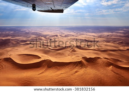 Beautiful landscape of the Namib Desert under the wing of the aircraft at sunset. Flying on a plane over the desert is one of the most popular tourist attractions in Namibia