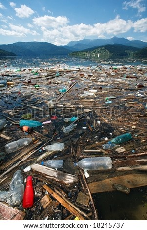beautiful landscape ruined by floating garbage, wide angle and dynamic view - stock photo
