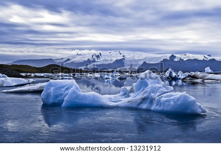 Beautiful landscape scenery with a floating iceberg in the foreground and a glacier in the background; Jökulsárlón; Iceland - stock photo