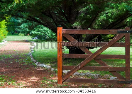 Beautiful landscape with a wooden fence at the entrance to a green garden - stock photo