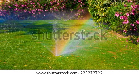 beautiful landscape with automatic  sprinkler spraying  watering the lawn in the home garden with a rainbow in water drops - stock photo