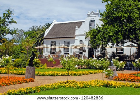Beautiful landscape with colonial farm house, patio and flowers in the garden(South Africa) - stock photo