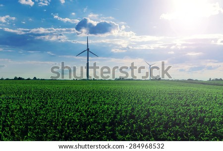 Beautiful landscape with fresh green grass, blue sky and windmills on the field - stock photo