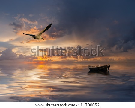 Beautiful landscape with lonely boat and birds against a sunset, majestic clouds in the sky - stock photo