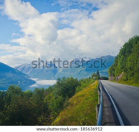 Beautiful landscape with norwegian road, fjord and mountains - stock photo