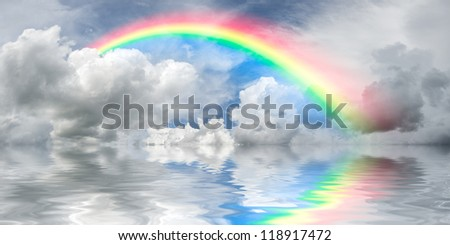Beautiful landscape with rainbow appearing from the majestic clouds and reflection in water - stock photo