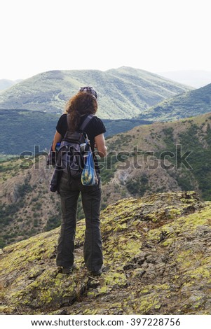 Beautiful landscape with young woman in high mountain