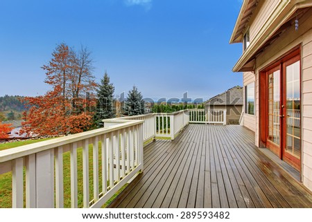 Beautiful large backyard with deck, lots of grass, and a view. - stock photo