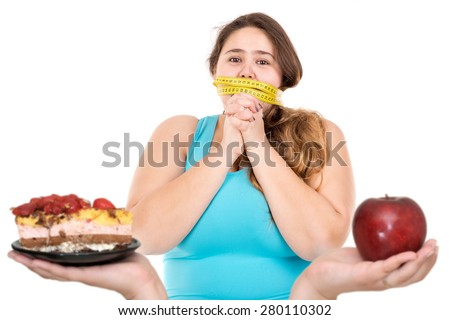 Beautiful large girl gagged with measuring tape looking at a cake and an apple isolated in white - stock photo