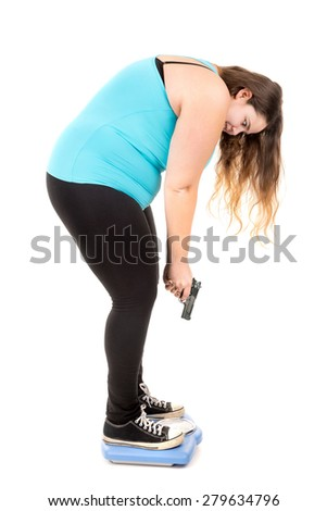 Beautiful large girl over a weight scale with a gun isolated in white - stock photo