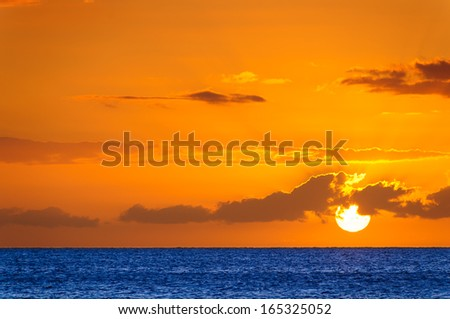 Beautiful large red sunset over the Pacific Ocean behind colorful clouds on Maui, Hawaii, USA - stock photo