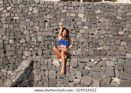 Beautiful latin black hair girl crazy on a stoned wall in vacation time with unusual position. Cute body and smile.