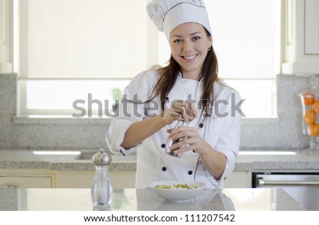 Beautiful latin chef adding salt and pepper to a dish - stock photo