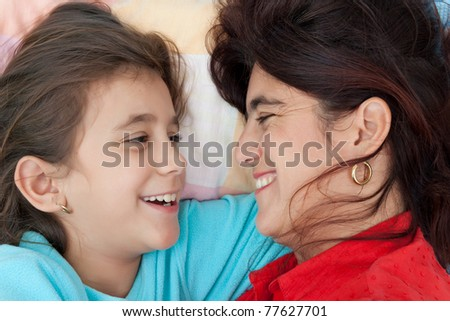 Beautiful latin mother and daughter smiling with love at each other - stock photo