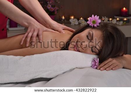 Beautiful latin woman getting bag massage at beauty center spa on warm ambient. - stock photo