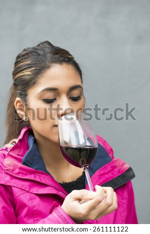 Beautiful latin woman smelling red wine over gray background.