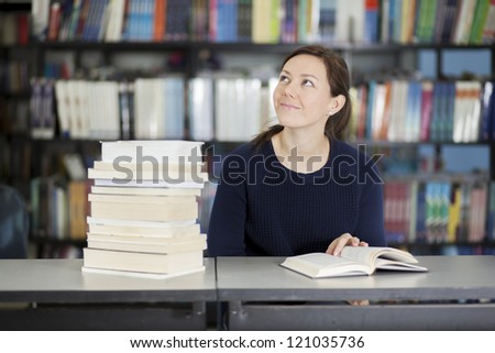 Beautiful latin woman thinking and looking to copy space while reading in the library - stock photo