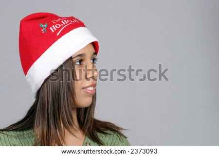 Beautiful latina girl in Santa hat looking to her left - stock photo