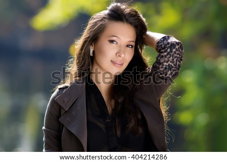 Beautiful latinonos woman in casual wear  walking on the park. Fashionable girl enjoying the warmth of the sun.Happy girl posing and expresses positive emotions - stock photo