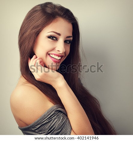 Beautiful laughing brunette woman with happy smile on with empty copy space. Toned closeup portrait - stock photo