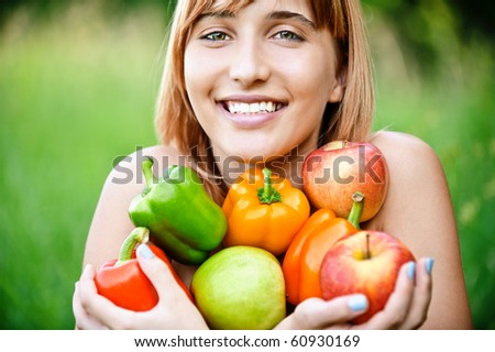 Beautiful laughing girl with apples and sweet pepper, on green summer background. - stock photo