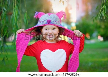 Beautiful laughing little toddler girl in a red coat and colorful knitted hat and scarf playing with yellow maple leaves in a sunny autumn park  - stock photo