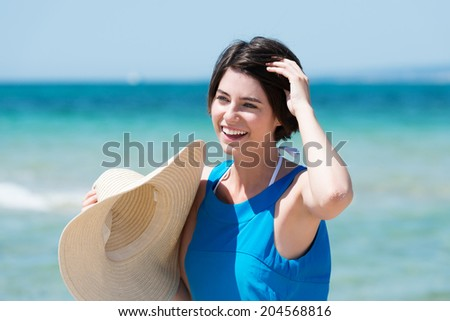 Beautiful laughing woman at the seaside standing in front of the ocean holding a wide brimmed straw sunhat with her hand to her short brunette hair - stock photo