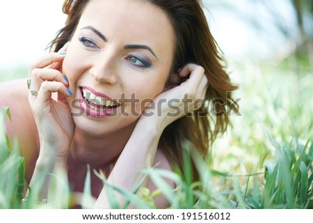 Beautiful laughing young woman in the park on a warm summer day