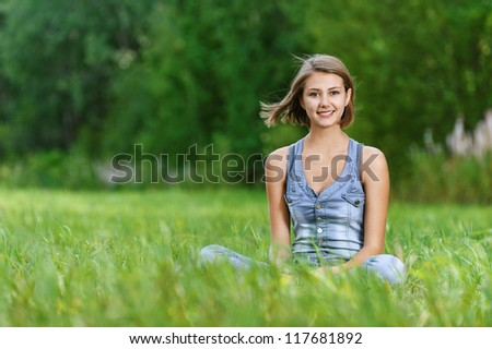 Beautiful laughing young woman sitting on grass, against background of summer green park.