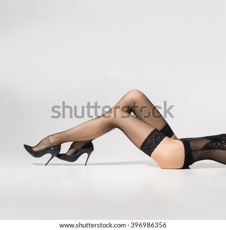 Beautiful legs in stockings over white background - stock photo