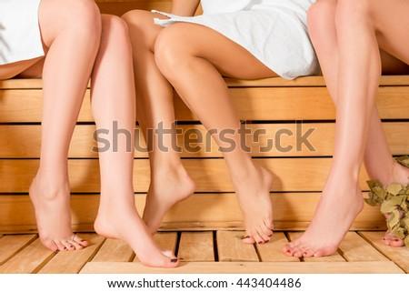 beautiful legs of three friends in a sauna closeup - stock photo