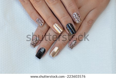 Beautiful leopard print nail art design with black  and golden background - stock photo